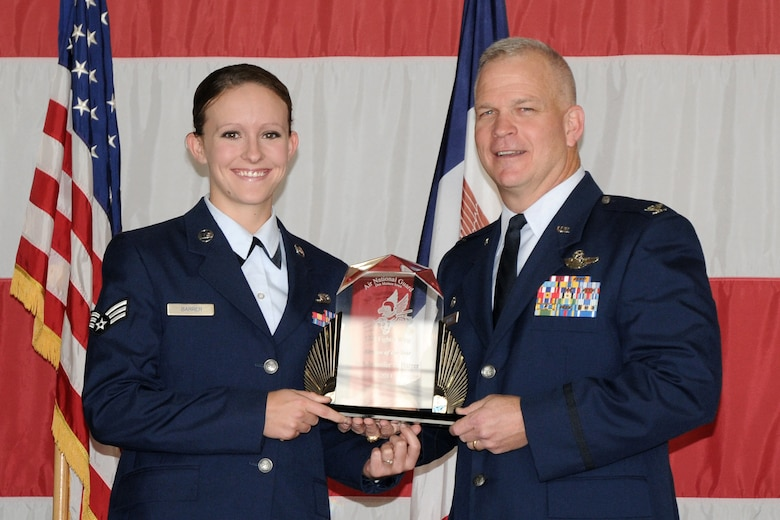 Col. Drew DeHaes (right) presents Senior Airman Jennifer Barrer (left) with the 2011 Airman of the Year award during the Awards Ceremony held in the hangar of the 132nd Fighter Wing, Des Moines, Iowa on November 6, 2011.  (US Air Force photo/Staff Sgt. Linda E. Kephart)(Released)