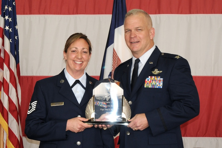 Col. Drew DeHaes (right) presents Tech. Sgt. Tina Bizios (left) with the NCO of the Year award during the 2011 Awards Ceremony held in the hangar of the 132nd Fighter Wing, Des Moines, Iowa on November 6, 2011.  (US Air Force photo/Staff Sgt. Linda E. Kephart)(Released)