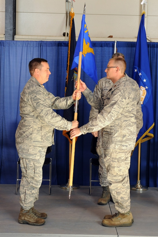 U.S. Air Force Maj. James Oaksford (right) takes the guidon from Col. Earl Evans during a ceremony held on 6 November 2011 at Hancock Field Air National Guard Base, Syracuse, NY, in which Maj. Oaksford assumed command of the 174th Fighter Wing's Civil Engineering Squadron.