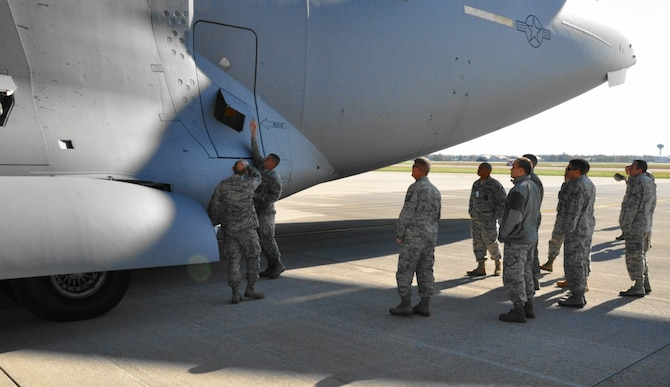 WRIGHT-PATTERSON AIR FORCE BASE, Ohio - Master Sgt. Kenneth Finch, an instructor with the 445th Civil Engineer Squadron, explains an exterior electrical outlet on the fuselage of a C-17 Globemaster III to a group of 445th firefighters. (U.S. Air Force photo/Master Sgt. Charlie Miller)
