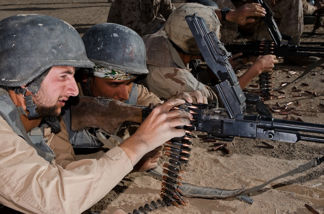 Students load a PKM general purpose machine guns during the firearms training portion of the Tactical Leaders Course aboard Camp Leatherneck, Helmand province, Nov. 1. The Joint Sustainment Academy Southwest has started a new course of training with various Afghan security forces with the idea of working together to accomplish a mission.