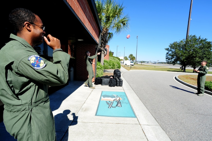 Staff Sgt. Kevin Sumlin tosses a football around with Security Forces Phoenix Raven's from McDill Air Force Base while waiting for transportation to their aircraft at Joint Base Charleston - Air Base Nov. 2.  Flying Crew Chiefs were trained in many specialized aircraft maintenance skills and provide universal support as the lone maintainer to fix most aircraft issues that may occur during a flying mission.  Sumlin is a flying crew chief with the 437th Aircraft Maintenance Squadron.  (U.S. Air Force photo/ Staff Sgt. Nicole Mickle)