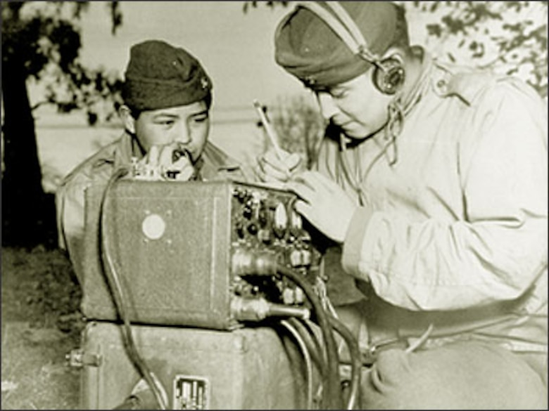 Private First Class Preston Toledo and Private First Class Frank Toledo, cousins and Navajos attached to a Marine Artillery Regiment in the South Pacific, relay orders over a field radio in their native tongue July 7, 1943. (U.S. Marine Corps photo/National Archives No. 127-MN-57875)