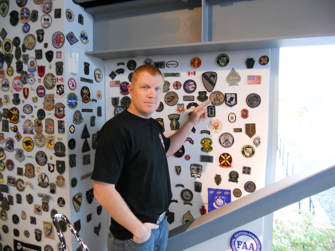 While visiting Paul Jr. Designs in Rock Tavern, N.Y., Staff Sgt. Patrick Mackey, 366th Logistics Readiness Squadron quality assurance inspector, points at a unit patch Sept. 27, 2011. Mackey was invited to Paul Jr. Designs after presenting the reality television star and custom motorcycle designer Paul Jr. Teutal with an American flag flown at 14 locations throughout Iraq. (Courtesy photo)