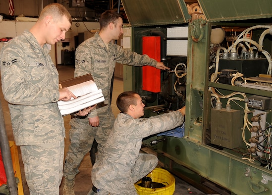 Airmen 1st Class Tyler Fornal, Steven Theodorou, and Richard Largey siphon out oil from one of their generators and check key components while performing routine maintenance at Cannon Air Force Base, N.M., Nov. 8, 2011. All three Airmen are technicians in the 27th Special Operations Civil Engineer Squadron power production shop, and are responsible for providing power to essential components on base. (U.S. Air Force photo by Airman 1st Class Alexxis Pons Abascal)