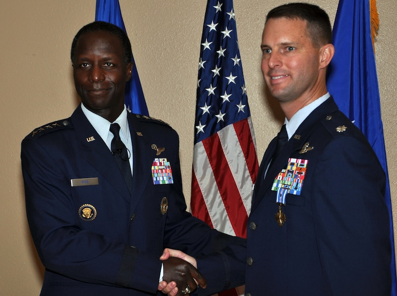 Gen. Edward A. Rice Jr., commander of Air Education and Training Command, congratulates Lt. Col. Gregory Roberts, 19th Air Force, after presenting him the Distinguished Flying Cross with valor at Randolph Air Force Base, Texas, Nov. 9. Roberts earned the award for actions he took while rescuing more than 1,000 people from severe flooding in Afghanistan in July 2010.