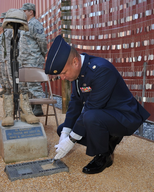 U.S. Air Force Maj. Cary Simpson, 349th Logistics Readiness Squadron plans officer, pours sand from Afghanistan onto a memorial during a ceremony at the Museum of the Forgotten Warrior outside of Beale Air Force Base, Calif., Nov. 10, 2011. The memorial was built to honor all of the servicemembers who have been killed during the Iraq and Afghanistan Wars as of October 30, 2011, containing over 6296 individual dog tags.  (U.S. Air Force photo by Staff Sgt. Jonathan Fowler/Released)