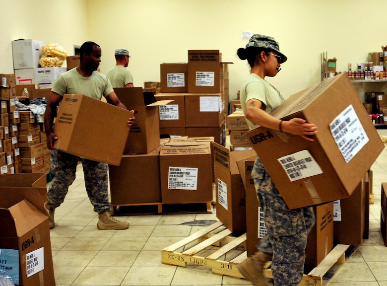 Army Spc. Marisol Landin, health care specialist, right, Staff Sgt. Christopher Middlebrooks, laundry and showers NCO, left, and Spc. Theodore Gigrich, wheeled vehicle mechanic, organize boxes of food at the dining facility at Joint Base Balad, Iraq, Oct. 15, 2011.  With the release of food services contractors, Airmen and soldiers joined together at the dining facility to feed the troops during the closure of JB Balad.    JB Balad has disassembled units, turned in equipment, and shut down services to transition the base to the Iraqi government. Landin is deployed from Fort Hood, Texas, and is from Jacksonville, Texas.  Middlebrooks is deployed from Joint Base McGuire-Dix-Lakehurst, N.J., and is from Edgewater Park, N.J. Gigrich is deployed from Fort Hood and is from Kalispell, Mont.  (U.S. Air Force photo/Master Sgt. Cecilio Ricardo)