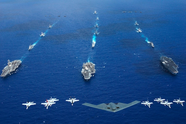 An Air Force B-2 bomber and 16 other aircraft from the Air Force, Navy, and Marine Corps fly over the USS Kitty Hawk (CV 63), USS Ronald Reagan (CVN 76), and USS Abraham Lincoln (CVN 72) carrier strike groups during a joint photo exercise (PHOTOEX) that kicks off exercise Valiant Shield 2006.  The Kitty Hawk Carrier Strike Group is currently participating in Valiant Shield 2006, the largest joint exercise in recent history.  Held in the Guam operating area June 19-23, the exercise includes 28 Naval vessels including three carrier strike groups.  Nearly 300 aircraft and approximately 22,000 service members from the Navy, Air Force, Marine Corps, and Coast Guard are also participating in the exercise.::r::::n::