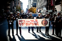 NEW YORK -- Marines from 2nd Battalion, 25 Marine Regiment, Marine Forces Reserve, carried a Toys For Tots banner in the annual New York Veterans Day parade, here, Nov. 11. This year marks the 92st Anniversary of The New York City Veterans Day Parade. The parade is hosted by the United War Veterans Council, Inc. on behalf of the City of New York. It is the oldest and largest of its kind in the nation. Since November 11, 1919, the parade has provided an opportunity for Americans and International visitors to honor those who have served in the nation's largest city. Sgt. Dakota Meyer, the recently awarded Marine Medal of Honor recipient, rode in the parade. Major Gen. Melvin Spiese, Deputy Commanding General, I Marine Expeditionary Force, represented the Marine Corps as one of the reviewing officials of the parade. The Toys For Tots program collects unopened toys each Christmas season for less fortunate children, see http://www.toysfortots.org/ for more information. (Marine Corps photo by Sgt. Randall A. Clinton / RELEASED)