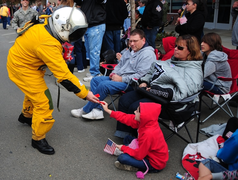 An Airman from the 9th Physiological Support Squadron, Beale AFB, Calif., hands candy to a local youth while wearing a full pressure suit during the Veterans Day Parade in Marysville, Calif., November 11, 2011. Full pressure suits are used while flying the U.S. Air Force U2 Dragon Lady intelligence, surveillance and reconnaissance aircraft. Many units from Beale showcased equipment used at the base. (U.S. Air Force photo by Airman 1st Class Shawn Nickel)