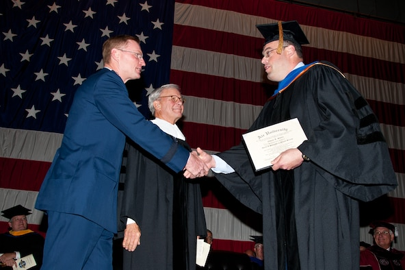 Lt. Col. Tadd Sholtis, right, deputy director of public affairs at Headquarters Air Combat Command at Langley AFB, Va., is presented the Air University's first Maxwell-conferred doctorate degree Monday by Lt. Gen. David Fadok, right, as AU honorary degree recipient Tom Brokaw looks on. (Air Force photo/Melanie Rodgers Cox)