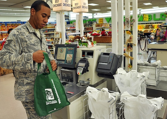 SPANGDAHLEM AIR BASE, Germany – Staff Sgt. Idris Royal, 52nd Force Support Squadron, picks up his re-usable grocery bag after checking out at the commissary here Nov. 15. The 52nd Fighter Wing's foreign object damage manager, in collaboration with base civilian agencies, provided re-usable grocery bags to Airmen and their families at the commissary in an effort to enhance recognition of the dangers loose debris have on the base's flying mission. (U.S. Air Force photo/Staff Sgt. Daryl Knee)