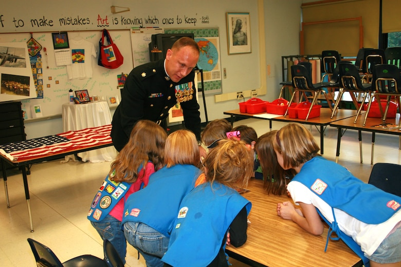 U.S. Marine Corps Maj. Jim Kokoszynski, American Legion and Veterans of Foreign War member, shows first grade students from Daisy Troop 60043 a photo of an F-15E Strike Eagle at Highland Elementary School, Highland, N.Y., Oct. 24, 2011. The Girl Scouts donated cookies to deployed Airmen and received a flag, which was flown during a mission supporting Operation Enduring Freedom, and was sent by U.S. Air Force Senior Master Sgt. Kevin Johnson, 366th Equipment Maintenance Squadron munitions materiel superintendent in appreciation for care packages sent to his squadron in Afghanistan. (Courtesy photo)