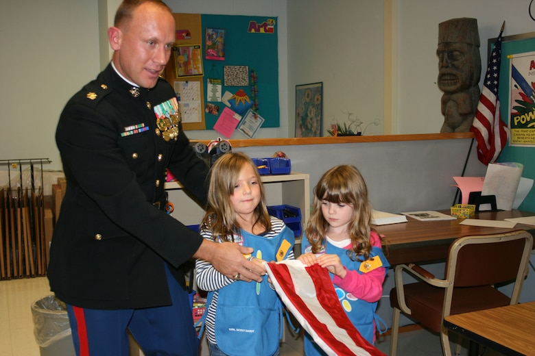 U.S. Marine Corps Maj. Jim Kokoszynski, an American Legion and Veteran of Foreign War member, helps Macayla Goodenough and Mckenzie Brooker fold their new American flag Oct. 24, 2011, at Highland Elementary School, Highland N.Y. The girls from Daisy Troop 60043 were sent the American flag by U.S. Air Force Senior Master Sgt. Kevin Johnson, 366th Equipment Maintenance Squadron munitions materiel superintendent, as a way of thanking the Girl Scouts for donating boxes of cookies to more than 400 members of his deployed unit. (Courtesy photo)