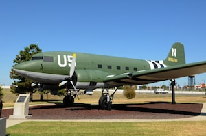 """Few aircraft were as well known or widely used during the 1940s as the C-47 Douglas """"Skytrain,"""" affectionately nicknamed """"Gooney Bird."""" The story of tail number N-2150761, the C-47 now on display in the Tinker Heritage Airpark, tells of the versatility of an aircraft that served its country well and the people who maintained it. The aircraft was based on the design of the Douglas DC-3 airliner, a commercial transport that appeared in 1936. The first C-47s were ordered in 1940 and, by the end of World War II, 9,348 had been  procured for military use. Douglas Aircraft Company produced 5,354 C-47s and spare parts for 500 more at its Oklahoma City Plant. Following the end of the war, the plant became Bldg. 3001, which is part of the Oklahoma City Air Logistics Center today."""
