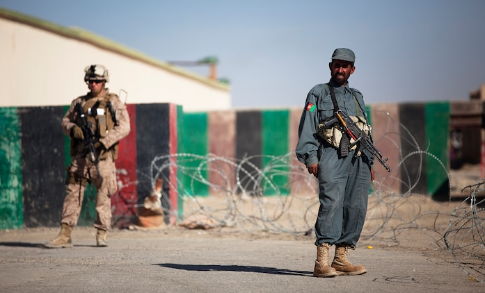 """GARMSIR DISTRICT, Helmand province, Afghainstan - Afghan National Police member Abdul Nabi provides security under the watchful eye of U.S. Marine 2nd Lt. Brenton Mastro, 24, the Guard Force Platoon commander for Headquarters and Service Company, 3rd Battalion, 3rd Marine Regiment, and native of Bedminster, N.J., during the funeral of District Chief of Police Lt. Col. Sayfullah Khan Rashidi here, Nov. 13. Sayfullah died when his vehicle was destroyed by an improvised explosive device that detonated while he traveled on a Garmsir road, Nov. 6. Two other ANP members were killed in the explosion, which occurred on the first day of the three-day Islamic festival of sacrifice Eid al-Adha. Amidst the challenging circumstances, 25-year-old District Governor Mohammad Fahim said Garmsir's stability remains unshaken by Sayfullah's death. """"Lt. Col. Sayfullah was brave and it's unfortunate we lost him, but we still have security and stability in Garmsir — this hasn't changed,"""" Fahim said.  Photo by Cpl. Colby Brown"""