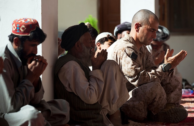 """GARMSIR DISTRICT, Helmand province, Afghanistan - U.S. Marine Lt. Col. Matthew J. Palma, the commanding officer of 3rd Battalion, 3rd Marine Regiment and native of Bristol, R.I., receives the prayer of a mullah, or local religious leader, in honor of fallen District Chief of Police Lt. Col. Sayfullah Khan Rashidi during his funeral here, Nov. 13. Sayfullah died after his vehicle was destroyed by an improvised explosive device that detonated while he traveled on a Garmsir road, Nov. 6. Two other ANP members were killed in the explosion, which occurred on the first day of the three-day Islamic festival of sacrifice Eid al-Adha. Amidst the challenging circumstances, 25-year-old District Governor Mohammad Fahim said Garmsir's stability remains unshaken by Sayfullah's death. """"Lt. Col. Sayfullah was brave and it's unfortunate we lost him, but we still have security and stability in Garmsir — this hasn't changed,"""" Fahim said.  Photo by Cpl. Reece Lodder"""