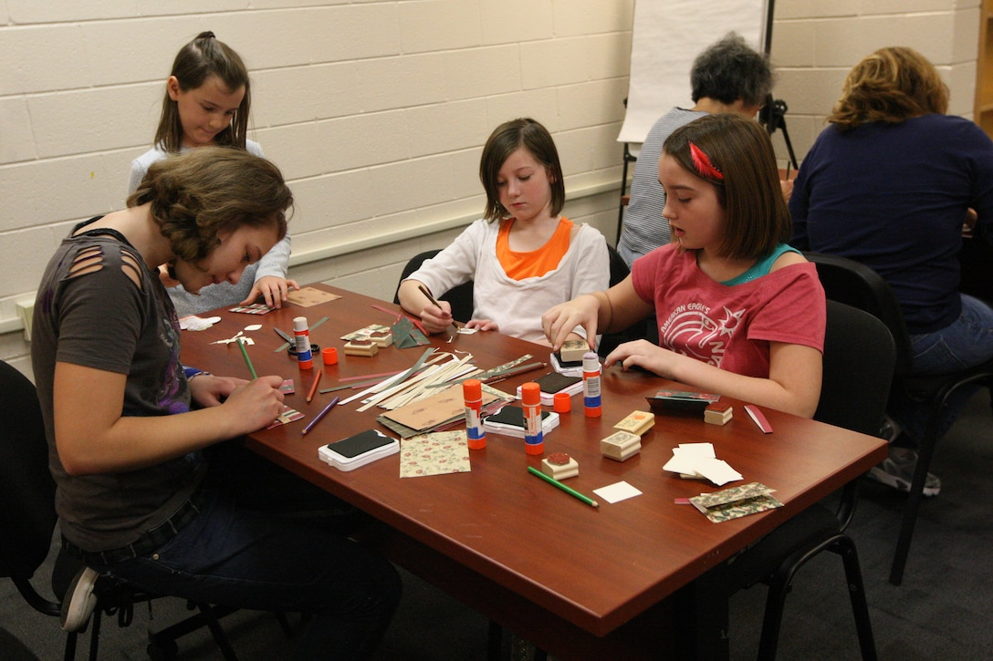 A group of military children craft gift tags and card holders during the Christmas Card workshop hosted by Marine Corps Community Services at Harriotte B. Smith Library aboard Marine Corps Base Camp Lejeune, recently. Two workshops were offered, both of which were fully booked.