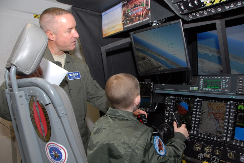 Donovan Benzin became a Guardsman for a day at the 107th Airlift Wing, Niagara Falls ARS. Lt. Col. Gregory Miller shows Donovan how to fly a C-130 aircraft on a simulator.