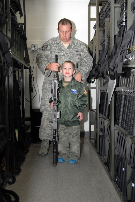 Five-year-old cancer survivor, Donovan Benzin became a Guardsman for a day at the 107th Airlift Wing, Niagara Falls ARS. Here he is touring the arms vault with Tech. Sgt Adam Piedmont. He would like to be a military policeman when her grows up.