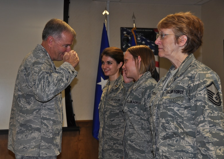 Brig. Gen. John P. McCoy, Wisconsin's assistant adjutant general for Air, salutes Staff Sgt. Samantha Swager, a 128th Air Refueling Wing services squadron technician, at the culmination of a five-day Health Services Inspection on Sunday, November 20, 2011.  Also present during the top performers award ceremony were 1st Lt. Kelly Iloncaie-Zelenski and Master Sgt. Kimberly Craddock.  Air Force inspectors completed a comprehensive review of the 128th Air Refueling Wing's medical group over the course of four days, and on the fifth day, the medical group was awarded an 'Excellent' rating.  Air National Guard photo by Staff Sgt. Jeremy Wilson.