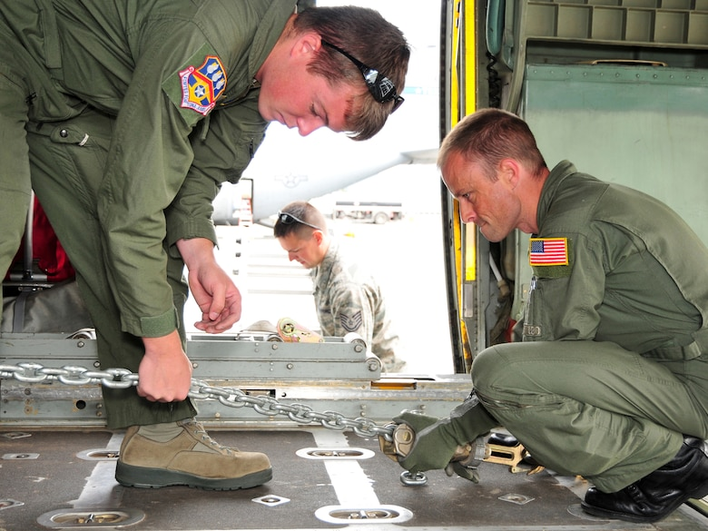 Tech. Sgt. Daniel Wormley (left), a flight engineer from the Kentucky Air National Guard's 165th Airlift Squadron, helps loadmaster Master Sgt. Clint Stinnett secure a communications truck to the floor of a C-130 aircraft with chains. The truck was bound for Volk Field, Wis., to be used in Operation Joint Patriot. (U.S. Air Force photo/Staff Sgt. Jason Ketterer)