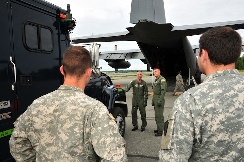 Master Sgt. Clint Stinnett and Staff Sgt. Jerry Passafiume, loadmasters from Kentucky Air National Guard's 165th Airlift Squadron, size up a communications truck July 10, 2011, in Anchorage, Alaska, before marshaling it onto a C-130 Hercules aircraft. The truck was bound for Volk Field, Wis., to be used in Operation Joint Patriot. (U.S. Air Force photo by Staff Sgt. Jason Ketterer)