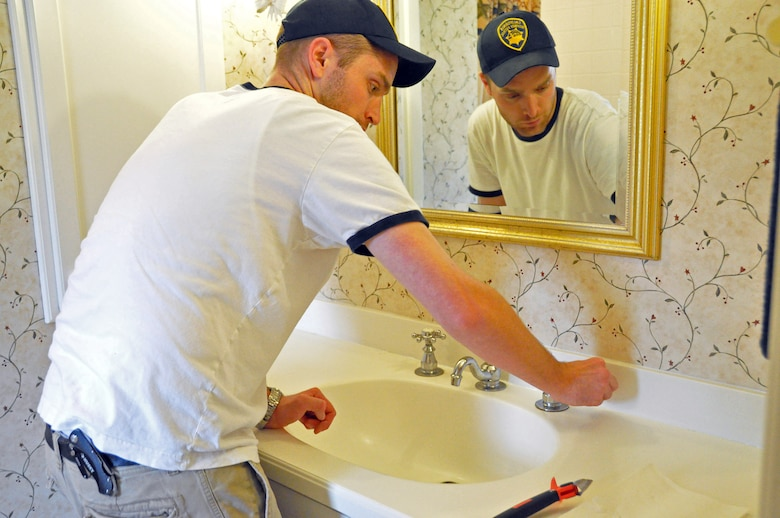 Joshua Henderson, one of 66 volunteers that renovated the Travis Fisher House, re-caulks the bathroom sinks throughout the house Nov. 18. The Fisher House provides a respite for family members of patients staying at David Grant USAF Medical Center, free from financial stress. (U.S. Air Force photo/Airman Madelyn Ottem)