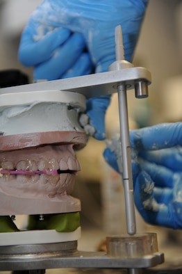 SPANGDAHLEM AIR BASE, Germany – Sgt. Victor Estupinan, 52nd Dental Squadron dental lab technician, mounts a cast to a vice to simulate a patent's bite here Nov. 22. The 52nd DS provides support to Saber Airmen and their families by promoting oral health and delivering professional dental care. (U.S. Air Force photo/Airman 1st Class Matthew B. Fredericks)