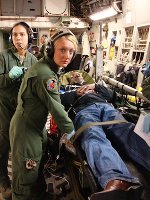 "Senior Airmen Ginnette Lykins (left) and Elyse Detling, both medical technicians assigned to the 445th Aeromedical Evacuation Squadron here, listen intently as they receive instructions after securing a simulated patient to a litter during a training flight on board a C-17 Globemaster III Nov. 17. The ""volunteer"" heart attack victim was James Chappel, a member of the Air Force Materiel Command Community Liaison Program, representing Tinker AFB, Okla. Twenty-one members of the group flew on the C-17 to experience first-hand how members of the squadron train for real-world missions. (U.S. Air Force photo/Ron Fry)"