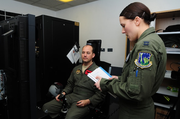 ROYAL AIR FORCE LAKENHEATH, England - Capt. Ashley Thomas, 48th Aerospace Medicine Squadron aerospace and operational physiology officer in charge, briefs Lt. Col. Jonathan Taylor, 494th Fighter Squadron director of operations, before training in the Reduced Oxygen Breathing Device/Hypoxia Familiarization Trainer, Nov. 18, 2011. The trainer provides aircrew members the ability to still experience a simulated altitude change without the added pressure changes and risks when using an altitude chamber. (U.S. Air Force photo by Senior Airman Lausanne Morgan)