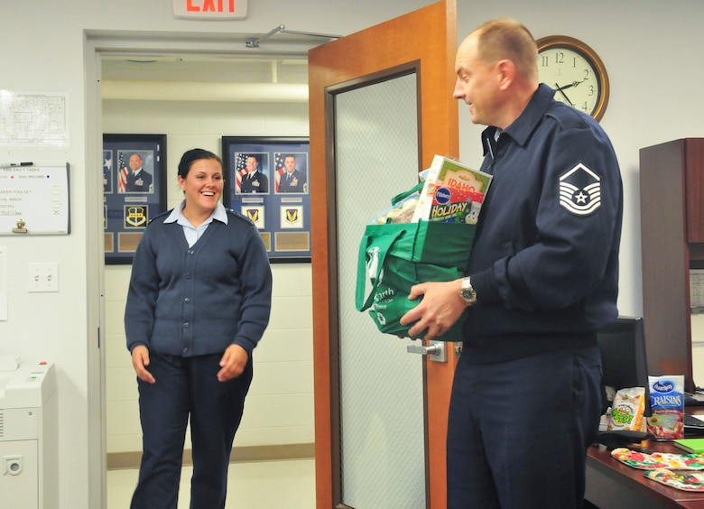 Master Sergeant Don Franken, a Beale first sergeant, surprises Senior Airman Sandra Healy with a bag of food Nov. 21, 2011 for the upcoming Thanksgiving holiday. The bag contained various side dishes, desserts and a sixteen pound turkey. (U.S. Air Force photo by Staff Sgt. Tinese Jackson/Released)