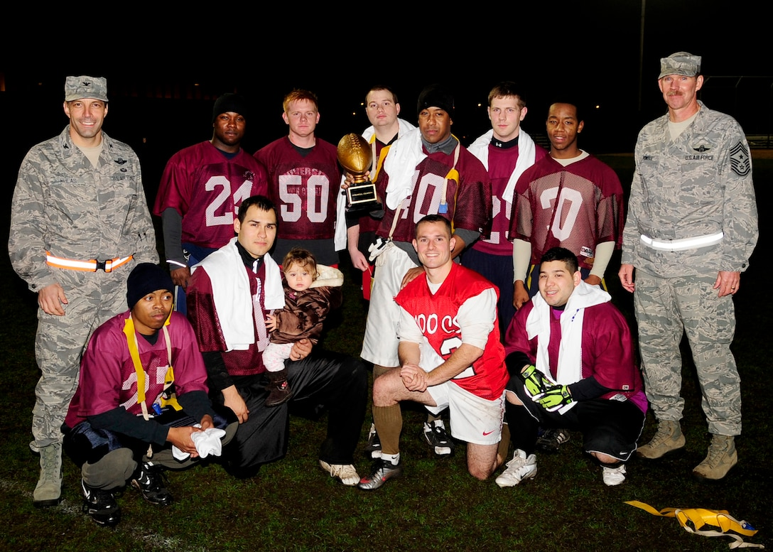 RAF MILDENHALL, England – Col. Christopher Kulas, 100th Air Refueling Wing commander, and Chief Master Sgt. Christopher Powell, 100th ARW command chief, pose with the 100th Communications Squadron football team after the team won the championship intramural football game here Nov. 23, 2011. The 100th CS team played against the 100th Maintenance Squadron and won the game 8-0. (U.S. Air Force photo/Senior Airman Ethan Morgan)