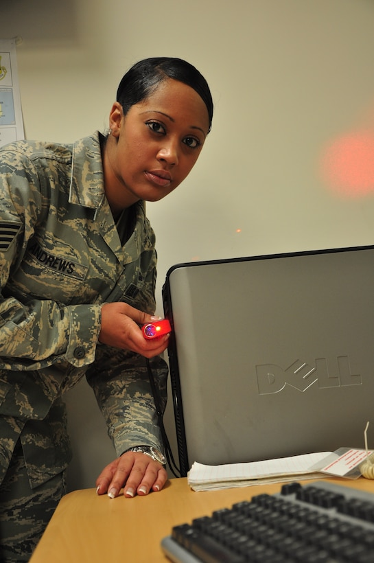 As part of Staff Sgt. Antwaynete Andrews' duties as Emissions Security NCOIC she ensures classified computers and telephones are far enough from unclassified items by using a laser measuring device, as shown in this photograph. (U.S. Air Force photo/Tech. Sgt. Chad Thompson)