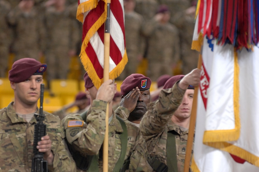 """Command Sgt. Maj. Terry Gardner, 4th Brigade Combat Team (Airborne), 25th Infantry Division, salutes during the playing of the national anthem during the 4-25th ABCT's deployment ceremony at Sullivan Arena, Anchorage, Alaska, Nov. 29, 2011.  The 4-25th ABCT, """"Spartan Brigade,"""" will deploy 3,500 Soldiers on a series of flights in November and December en route to Afghanistan. (U.S. Air Force photo/Staff Sgt. Zachary Wolf)"""