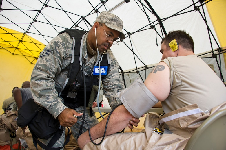 Air National Guard Staff Sgt. James Gill, left, 116th Medical Group (MDG) medical technician, Robins Air Force Base, Ga., checks the vital signs of a first responder in the recovery tent during Operation Sunrise Rescue at Camp Blanding Joint Training Center, Fla., Nov. 18, 2011.  The 116th MDG received a perfect score in the joint force exercise to test their skills as a Chemical, Biological, Radiological, Nuclear, and High Yield Explosive Enhanced Response Force Package.  (National Guard photo by Master Sgt. Roger Parsons/Released)
