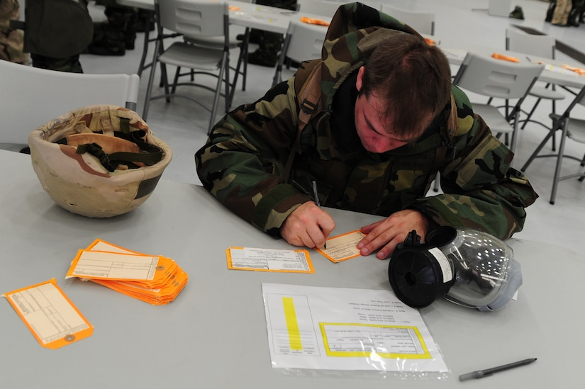 Staff Sgt. Richard Barie fills out a Gas Mask inspection tag during the Ability To Survive and Operate Rodeo at Nose Dock One at Joint Base Charleston - Air Base Nov. 28.   The rodeo was held to help prepare more than 700 Airmen for the upcoming JB Charleston Operational Readiness Inspection. The rodeo included  Self Aid Buddy Care, weapons familiarization, Unidentified Explosive Objects training and donning chemical protection gear.  Barie is from the 628th Logistics Readiness Squadron.  (U.S. Air Force photo/ Staff Sgt. Nicole Mickle)