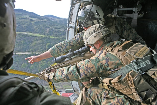 Gunnery Sgt. Jakub Biziorek, the platoon sergeant for the sniper platoon, Headquarters and Support Company, 2nd Battalion, 1st Marine Regiment, listens to his spotter as he points out different targets for him to sight in on while flying in a Navy Sikorsky HH-60H Rescue Hawk over Camp Horno, Nov. 29.  The spotters learned the importance of communication from this type of training because they have to be in constant contact with the shooter, crew chief and pilot to give the shooter the best opportunity for accuracy.