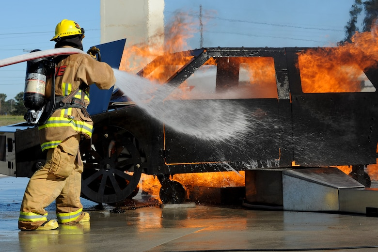 VANDENBERG AIR FORCE BASE, Calif. – A student firefighter from Allen Hancock College Fire Academy puts out a car fire during training at the Turner Bell Fire Training Campus here Wednesday, Nov. 30, 2011. . Allen Hancock College students trained at Vandenberg to help build the required skills while their Public Safety Complex, which will incorporate skill training facilities, is under construction. (U.S. Air Force photo/Staff Sgt. Levi Riendeau)