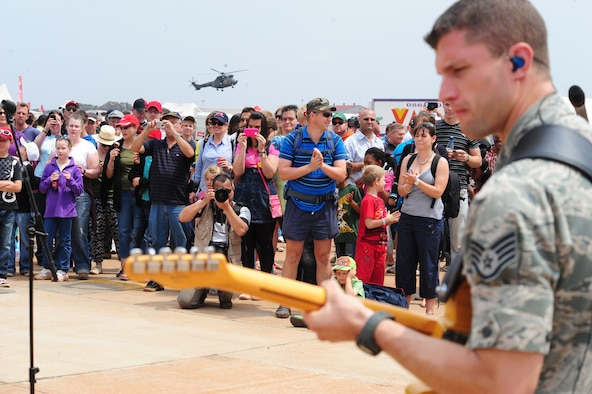 """PRETORIA, South Africa - Staff Sgt. Dustin Trimble, U.S. Air Forces Europe Band """"Touch 'n Go"""" lead guitarist performs while visiting South Africans look on and an aerial demonstration is shown in the distance during the 2011 Air Show & Lifestyle Expo at Waterkloof Air Force Base, Oct. 1. The band performed two one-hour sets, which drew crowds that danced, sang and enjoyed some good old rock and roll music. (U.S. Air Force photo by Tech. Sgt. Todd Wivell)"""