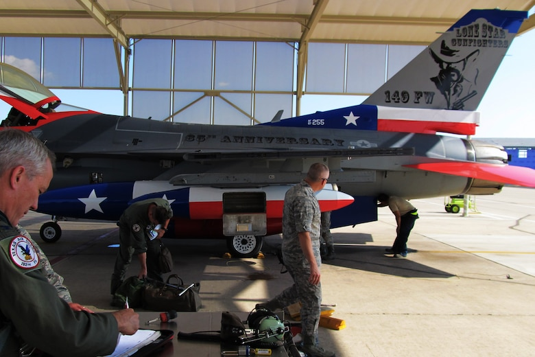 The Texas Air National Guard's 149th Fighter Wing's flagship F-16 returning to Lackland Air Force Base after being painted to honor the 65th anniversary of the unit's affiliation with the Air National Guard, Sept. 29, 2011.  Colonel (Col.) John Kane (left), wing commander, preparing the aircraft's forms for return to maintenance personnel.  (Air National Guard photo by Staff Sgt. Phil Fountain/Released)