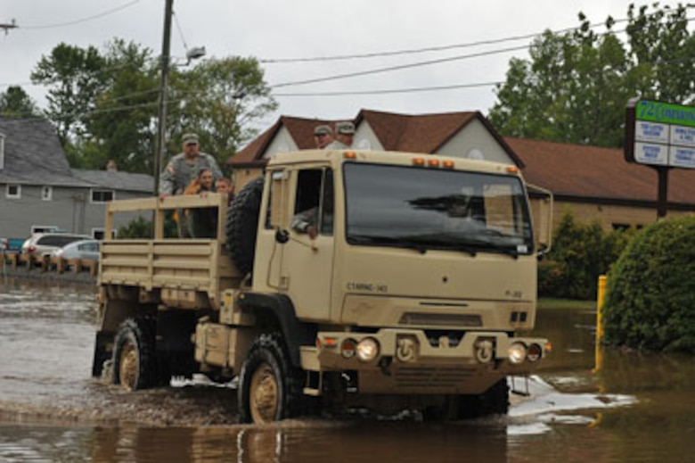 Members of the 143rd Military Police Company, Connecticut Army National Guard, help a Bristol family stranded in their home by flood waters to safety on Aug. 28, 2011 after flooding caused by Irene. (Photo courtesy 143rd Military Police Company, CTARNG)