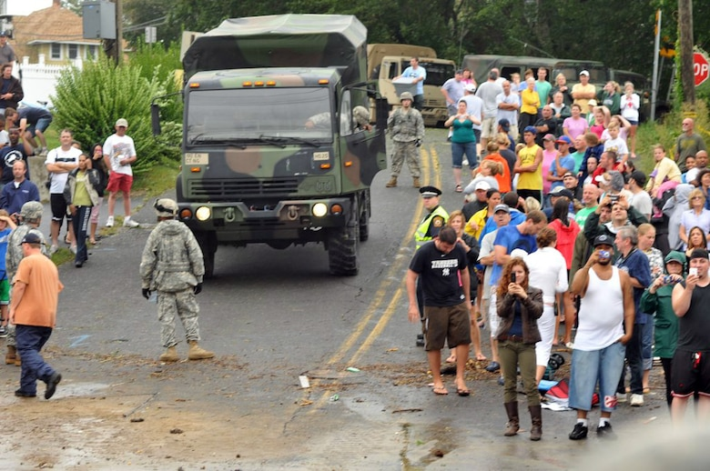 Members of the 192nd Multi-Functional Engineer Battalion, Connecticut Army National Guard guide a vehicle through the crowd looking at flooding along the shore in the aftermath of Hurricane/Tropical Storm Irene on Aug. 28, 2011. The engineers were among many Connecticut Guardsmen called out to assist local authorities before, during and after the storm battered the coastline. (U.S. Army photo by Capt. Chuck Taylor)