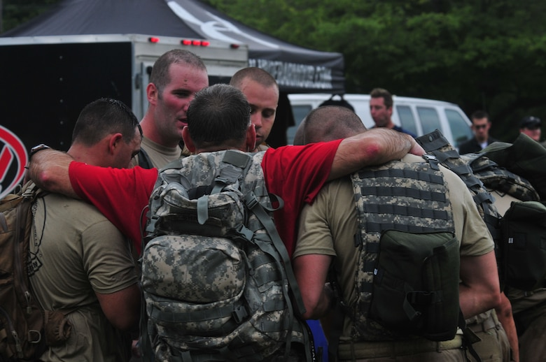 Chief Master Sgt. Tim Shaw (red t-shirt) huddles with exhausted members of the Connecticut Air National Guard Emergency Service Team during the annual Connecticut SWAT Challenge event at the West Hartford MDC Reservoir Aug. 25, 2011. The Guard team took 22nd place overall in the annual competition and earned the Top Military Team award for the second consecutive year. (U.S. Air Force photo by Tech. Sgt. Erin McNamara)