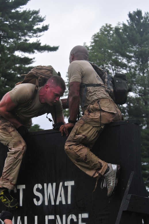 Staff Sgt. Brian Davies (left), 103rd Security Forces Squadron, and Staff Sgt. Victorious Felder from 103rd Air and Space Operations Group scale a wall during a Connecticut SWAT Challenge event at the West Hartford MDC Reservoir in Conn. Aug. 25, 2011. The Guard team took 22nd place overall in the annual competition. (U.S. Air Force photo by Tech. Sgt. Erin McNamara)