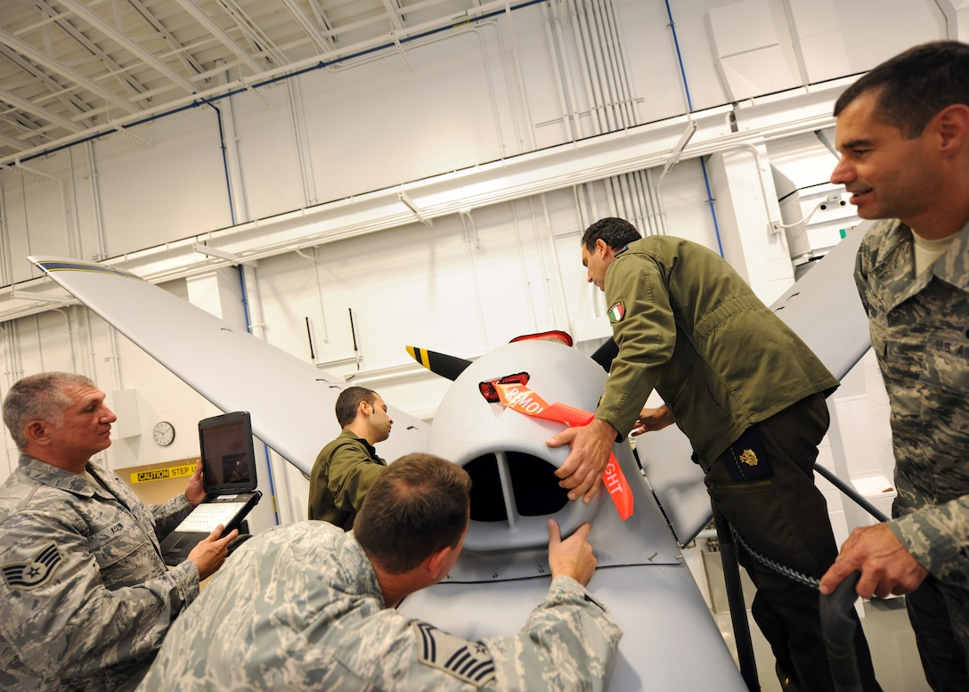 Italian Air Force Chief Warrant Officer Lorenzo Scafuto (second from right) and Staff Sgt. Marco Redavide (second from left) replace the MQ-9 engine cover during a training class at Hancock Field's MQ-9 Field Training Detachment (FTD) in Syracuse NY, on 20 Sept 2011.  Scafuto and Redavide are the first foreign military members to receive formal training on the MQ-9 at Hancock Field. (Photo by Staff Sgt Ricky Best)
