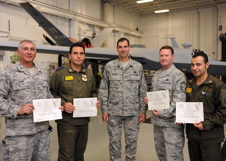 Italian Air Force Chief Warrant Officer Lorenzo Scafuto (second from left) and Staff Sgt. Marco Redavide (right), representing the first foreign military gradutates of Hancock Field's MQ-9 maintenance schoolhouse, receive certificates of training during a ceremony held in Syracuse, New York on 21 Sept 2011.  Also receiving certificates from instructor Master Sgt. Scott Simpson (center) are Senior Master Sgt. James Davison (second from right) and Staff Sgt. Scott Koor (left). This was the 100th graduating class from Hancock Field's MQ-9 Field Training Detachment. (Photo by Staff Sgt Ricky Best)