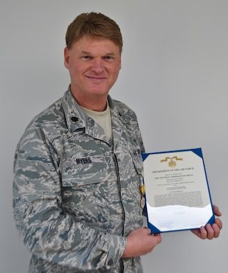 Lt. Col. Christopher Myers, a chaplain with the 128th Air Refueling Wing, presents an Air Force Commendation Medal and accompanying first Oak leaf cluster following the medal's presentation on Saturday, October 1, 2011.  Chaplain Myers received the first Oak leaf cluster for his accomplishments during an overseas deployment in 2010, wherein he was responsible for 15 worship services and an ongoing educational class.  U.S. Air Force photo by Staff Sgt. Jeremy Wilson