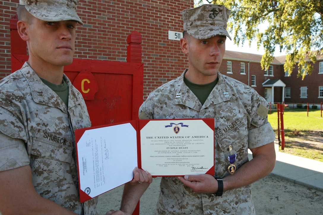 (left to right) Capt. John E. Shubeck, company commander, Company C, 2nd Combat Engineer Battalion, 2nd Marine Division, presents the Purple Heart to Capt. Chase B. Wheeler, executive officer, Company C, 2nd CEB, aboard Marine Corps Base Camp Lejeune, N.C., Oct. 3. Wheeler received the Purple Heart for injuries sustained from an approximately 120-pound improvised explosive device in Helmand province, Afghanistan.